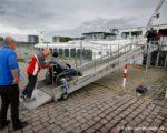 Rolstoelers van de PWA boot worden aan land gebracht