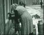 Beeld uit film 1942 Bouwhuis: Mevr. Bouwhuis van de Tielse Melkinrichting maakt de stoep ijsvrij