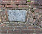 De sluitsteen boven de dichtgemetselde poort verraadt dat Van Oosterhoudt hier in 1802 een nieuwe ingang maakte voor zijn bedrijf.